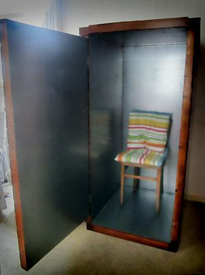 man-sized upright wooden cabinet with hinged door, just enough room for a chair